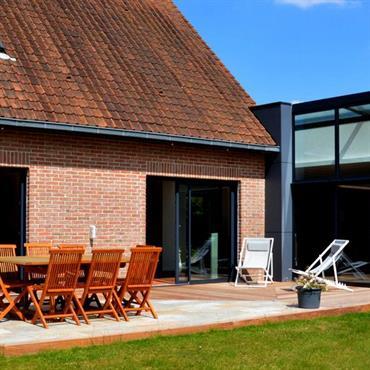 Terrasse avec sol en bois et coin repas en pierre.