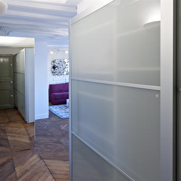 Une entrée agrandie  Pour agrandir l'entrée et effacer le meuble de cuisine ce dernier a été recouvert d'un miroir. L'entrée dispose également d'une grande penderie.