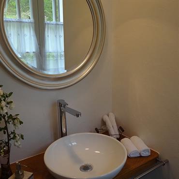 Salle de bain raffinée qui mêle le cachet de l'ancien et le confort des équipements contemporains avec sa vasque à poser ronde