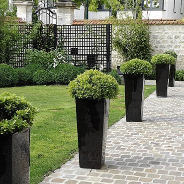 Jardin architecturé avec dallage en pavés de grès, jardinières et gazon.