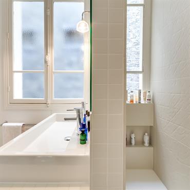 La salle d'eau offre une ambiance apaisante avec des carrelages blancs qui misent sur les effets de matière.