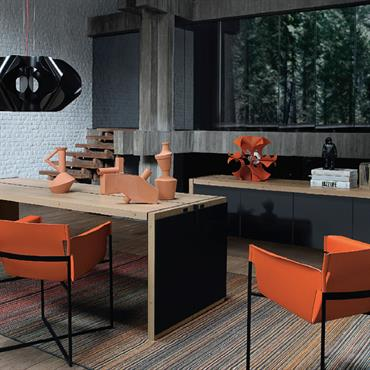 Bel arrangement de couleurs avec le bureau en bois naturel et les fauteuils en tissu orange