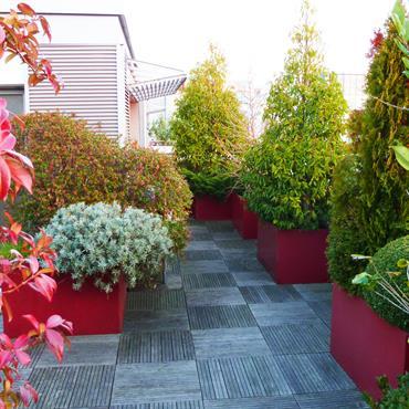 Terrasse en bois avec jardinières en métal rouge