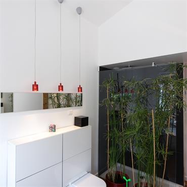 Un rideau de papyrus se place devant la paroi de douche italienne. D'une profondeur d'1,4m la douche n'a pas de porte. Le carrelage noir lui donne un aspect plus contemporain ...