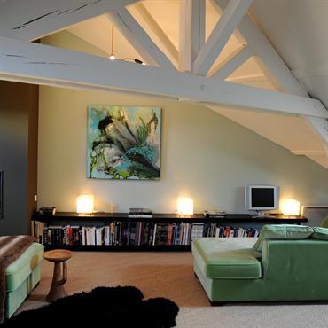 Aménagement du salon dans les combles, avec poutres repeintes en blanc pour moderniser