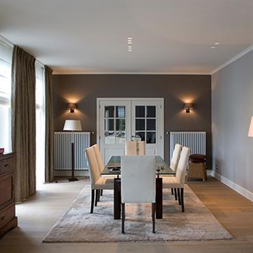 Salle à manger avec commode ancienne. Table rectangulaire et chaises en cuir blanc. Murs taupe et gris claire
