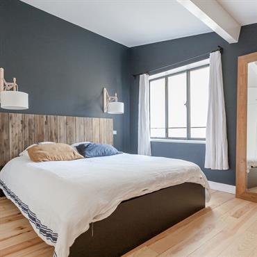 Chambre aux murs sombres et tête de lit en bois