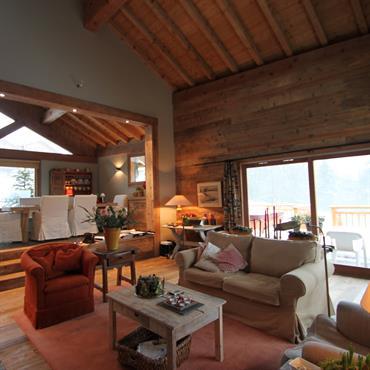 Salon chaleureux dans un chalet, ouvert sur la salle à manger, en retrait par la différence de niveaux