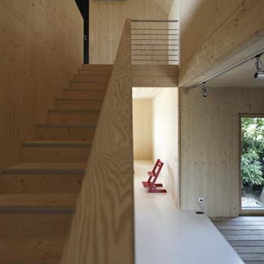 En cohérence avec l'ensemble de la maison faite de en panneaux de bois massif et de matériaux écologiques, cet escalier offre un rendu