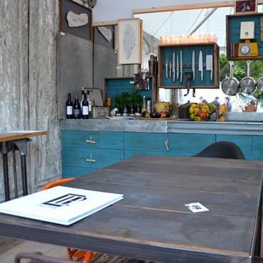 Cuisine généreuse par une décoration riche et colorée. Meuble En bois lasure bleue. Table en bois structure inox. Mur en bois gris poncé.