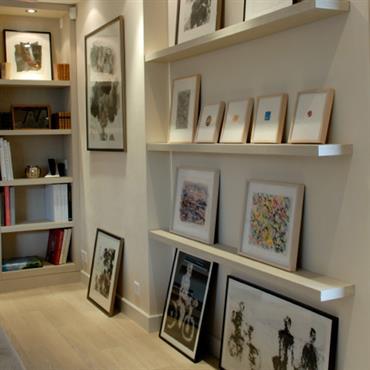 Le mur habillé d'étagères permet de personnaliser la pièce avec différents cadres et bibelots.
