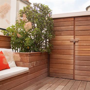 Terrasse en bois avec banquette et petit cabanon rustique