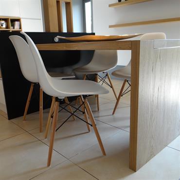La table de cuisine en bois clair prolonge l'îlot central, créant un coin repas confortable. Les chaises Eames blanches s'intègrent parfaitement à ce décor contemporain.