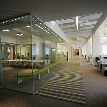 Bureaux en open space. Moquette pour l'isolation acoustique. Poutres apparentes, luminosité, couleurs claires.