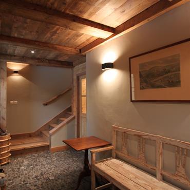 Couloir aménagé en espace d'attente. Banc en bois, poutres apparentes, murs blancs