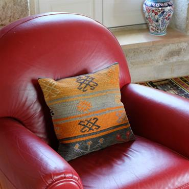 Housse de coussin en kilim sur canapé contemporain en cuir rouge