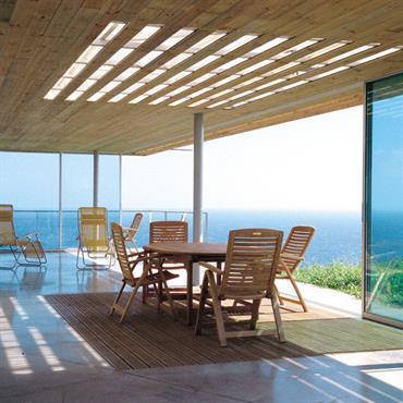 Terrasse avec vue sur la mer, toiture en bois ajourée