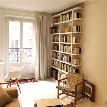 Salon moderne avec bibliothèque dans un appartement classique parisien