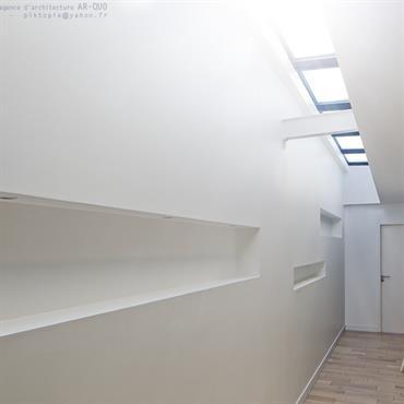 Couloir en lumière zénithale avec bureau.
