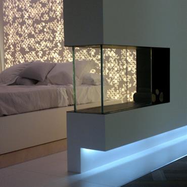 Chambre avec cheminée centrale qui sert de séparation. Lumière bleutée au raz du sol, le long du mur.