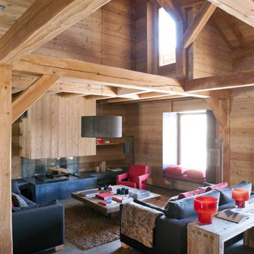 Le salon offre la chaleur et l'intimité de l'ambiance montagne grâce à ses volumes et à sa charpente apparente et présente une certaine fraicheur par son mobilier aux lignes contemporaines.