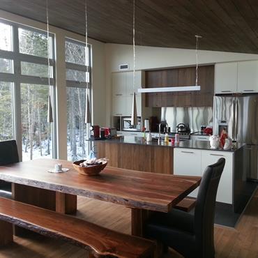 Cuisine ouverte sur la salle à manger. Table et bancs rustiques en bois