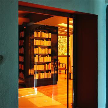 Une porte coulissante en verre orange s'escamote dans la double cloison derrière la bibliothèque et sépare la cuisine du séjour - véranda.