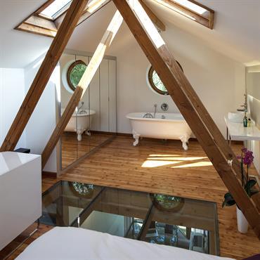 La chambre est accessible par un escalier. Le meuble sert de rangement et de garde corps. La charpente sépare la partie chambre de la partie bain.