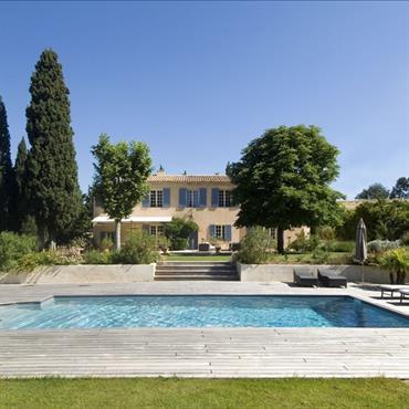 Depuis la maison aux nombreuses ouvertures, vue sur le coin piscine qui est implanté sur la partie basse du terrain.