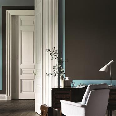 Coin bureau avec mur gris foncé, couleur d'accent bleu ciel et boiseries blanches équipé d'un bureau en bois de style ancien et d'un fauteuil de bureau