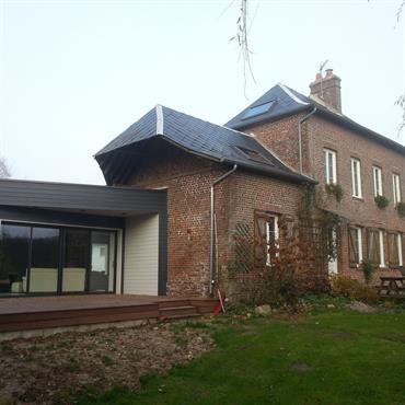 La maison existante en brique et ardoise est constituée d'un bâti principal centré avec deux ailes. Une extension contemporaine en toiture terrasse a été ajoutée avec de larges baies vitrées.
