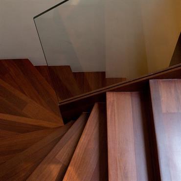Le bois sombre de cet escalier demi tournant fonctionne parfaitement avec le garde corps en verre.