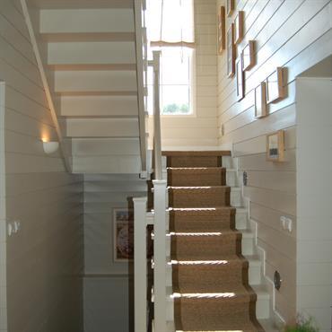Escalier en bois peint en blanc  et recouvert d'un tapis en jonc de mer.