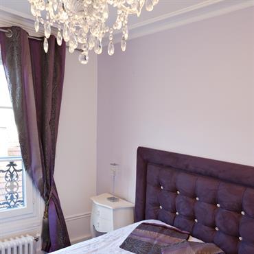Chambre classique aux couleurs contemporaines  Le couleur prune recouvre le molleton de la tête de lit et les rideaux pour leur donner une touche contemporaine.