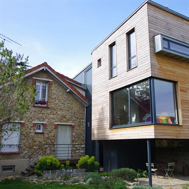 Maison contemporaine en bois et baies vitrées. Terrasse ombragée sous le plancher