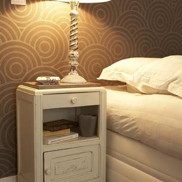 Table de chevet et lampe blanches sur papier peint graphique marron et or
