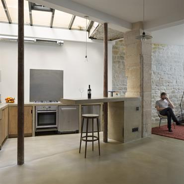 La grande pièce de vie réunit salon, salle à manger et cuisine positionnée sous l'autre verrière. Les différents espaces trouvent naturellement leur place dans le découpage orchestré par le plan ...