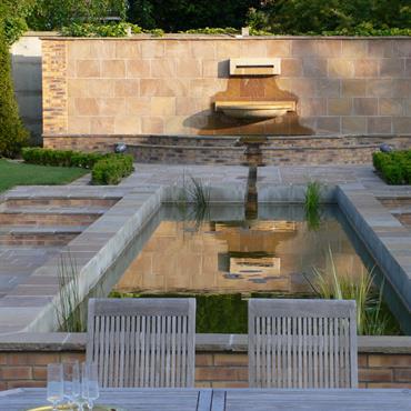 Bassin de jardin aux lignes géométriques intégré dans un jardin avec décrochés, escaliers, dalles de pierre et parties en gazon.