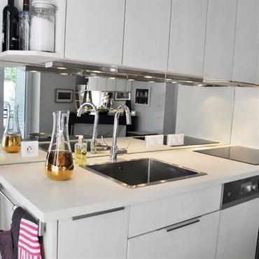 Petite cuisine blanche moderne avec miroir en guise de crédence