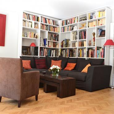 Salon avec bibliothèque. Murs blancs et étagères blanches. Canapé d'angle noir et fauteuils