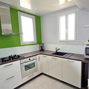 Cuisine moderne blanche rehaussée par le mur vert