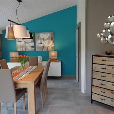 Salle à manger moderne, mur bleu en contraste avec la décoration orange. Couleurs claires et naturelles