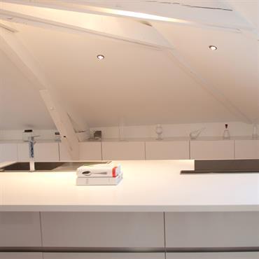 La cuisine a été dessinée sur mesure. Elle comprend un plan central de résine blanc pur de 4,5m de long.
