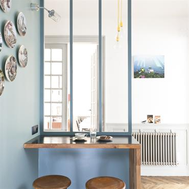 Coin repas de style industriel dans un environnement bleu. Table en bois