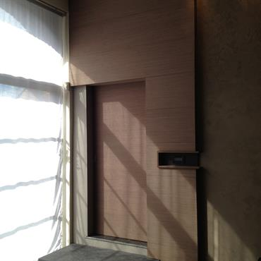 Entrée valorisée par un jeu de plans différents. La porte est en retrait par rapport au panneau en ressaut, les deux sont en bois massif. La marche détachée du sol ...
