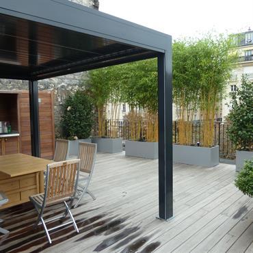 Terrasse de ville en bois exotique. Bacs en aluminium thermolaqué.  Pergola bioclimatique et cuisine d'extérieur.