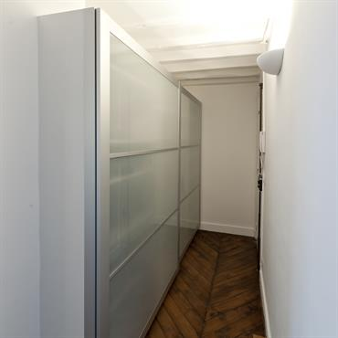 Penderie dans l'entrée L'entrée initialement généreuse permettait d'installer un grand rangement pour libérer les volumes des autres pièces. Ce rangement est accessible depuis l'entrée mais aussi depuis la chambre.