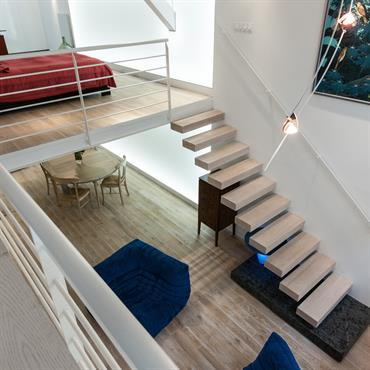 L'escalier suspendu en chêne blanchi qui monte à la mezzanine du loft est sans limon, sans grade corps, sans contremarche. La première marche en matrix sert aussi de table basse.
