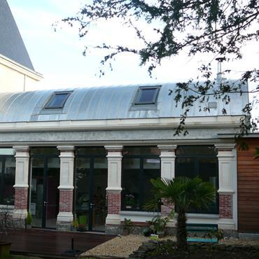Bâtiment de style classique, piliers blancs et briques, baies vitrées. Toiture en zinc
