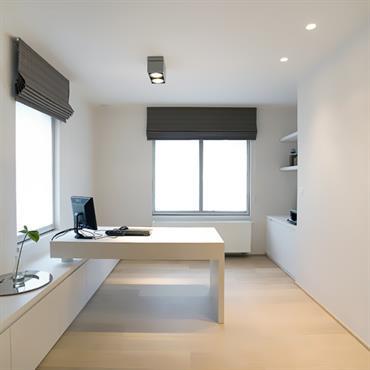 Bureau épuré avec murs et meubles blancs. Stores en tissus gris aux fenêtres